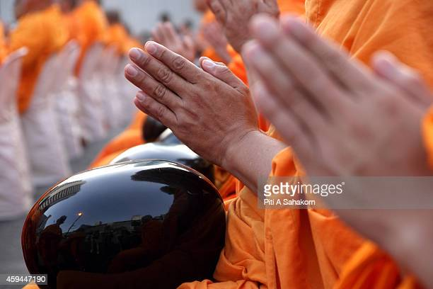 Buddhist monks during meditation before civilians drop dried food into their bowls at a shopping district in Bangkok Thousands of Buddhist monks took...