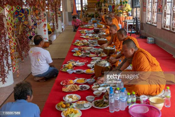 buddhist monks eating lunch at a temple. - tim bewer stock pictures, royalty-free photos & images