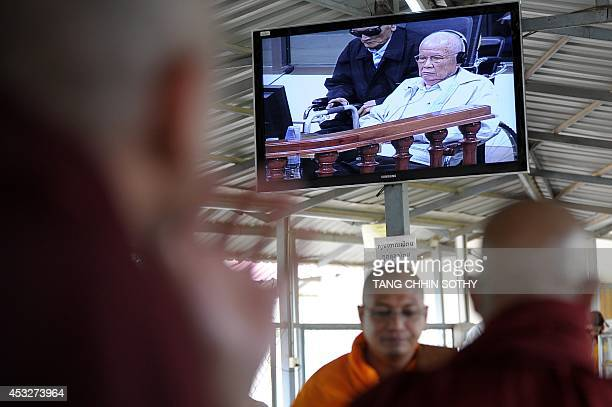 Buddhist monks from Myanmar watch a live video feed showing former Khmer Rouge leader 'Brother Number Two' Nuon Chea and former Khmer Rouge head of...