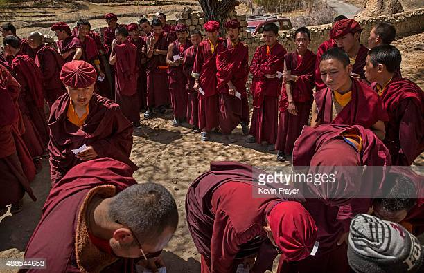 Buddhist monks from the Drukpa lineage hold their voting cards as they wait outside a polling station to vote near the Hemis Monastery on May 7 2014...