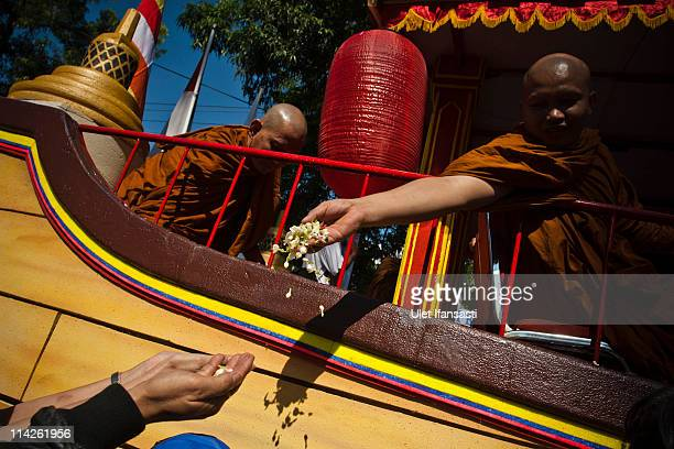 Buddhist monks give holy flower to Budhist members as join the procession from Mendut temple to Borobudur temple on Vesak Day commonly known as...