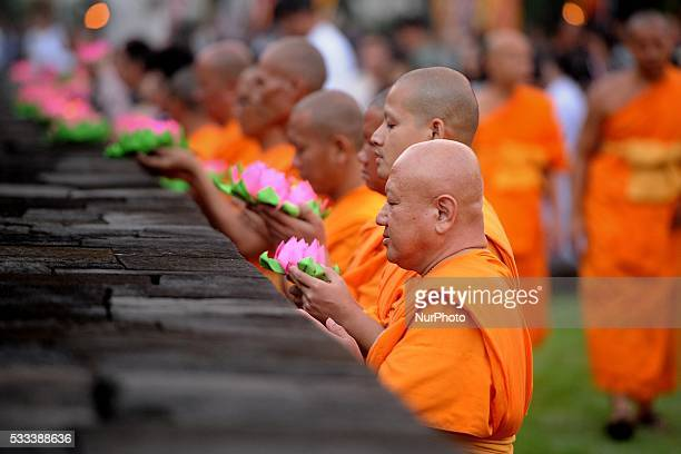 Buddhist monks hold lotus candles offerings while praying during Vesak day celebration at Borobudur Temple on May 22 2016 in Magelang Indonesia...