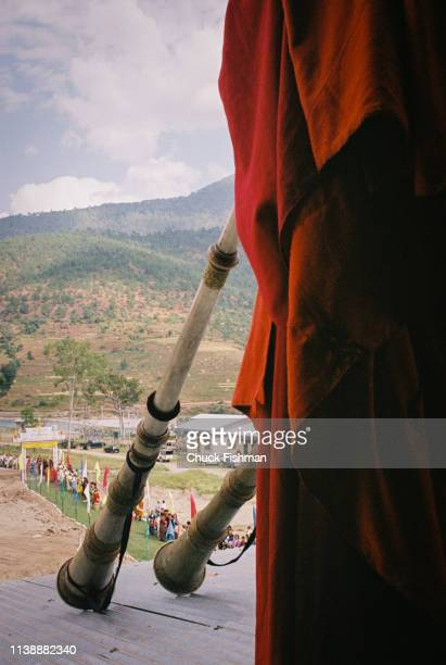 Buddhist monks in ceremonial attire playing dungs while awaiting Trulku Jigme Chode for his stop at the Khuruthang Lhakhang en route to his winter...