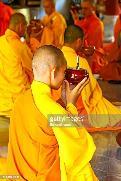 Buddhist monks in monastery at prayer before meal