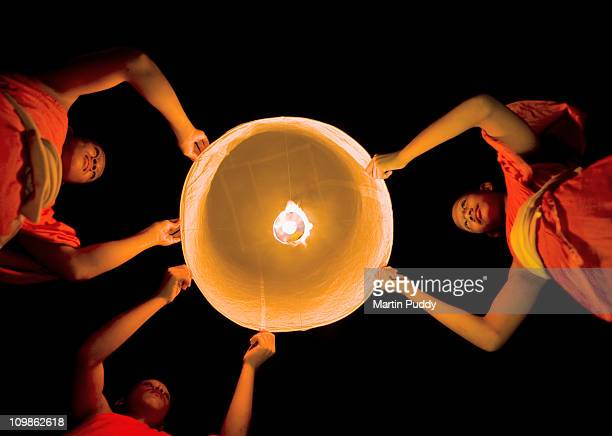 Buddhist Monks Launching a Khom Loy Lantern