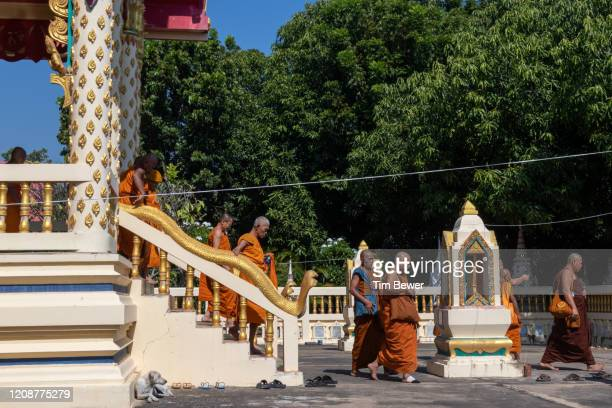 buddhist monks leaving ubosot after confessional meeting. - tim bewer fotografías e imágenes de stock