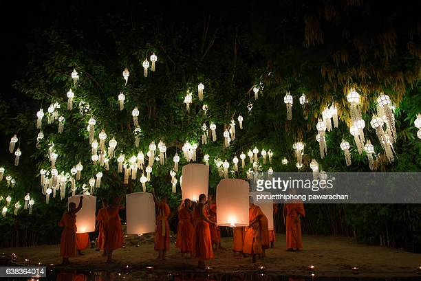 buddhist monks light the flying lanterns under a bodhi tree at the wat pan tao temple in chiang mai, thailand. - lanna stock pictures, royalty-free photos & images