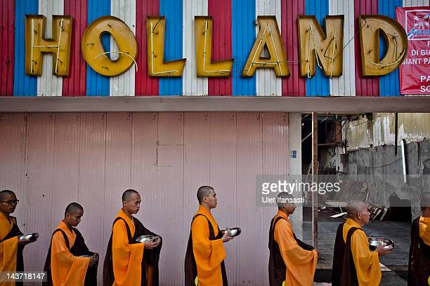 Buddhist monks line up as they walk around the streets for receive alms from Buddhist religious members of the public ahead of Vesak Day on May 3...