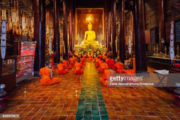buddhist monks meditate inside the wat phan tao, chiang mai - tempel stock-fotos und bilder