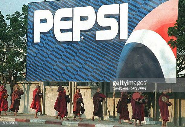 Buddhist monks on their late afternoon alms round walk in this 11 January 1996 file photo underneath a billboard advertising Pepsi cola which pulled...