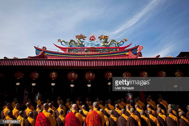 Buddhist monks pray before receiving alms from Buddhist religious members of the public ahead of Vesak Day on May 3 2012 in Magelang Indonesia...