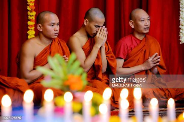 Buddhist monks pray during the 2606th 'Dhammacakka Pavattana' day celebrations at the Maha Bodhi Society in Bangalore on July 29, 2018. -...