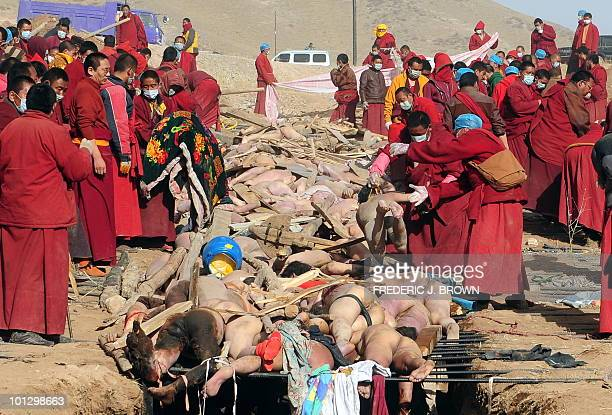 Buddhist monks prepare the bodies of earthquake victims for a mass cremation on a hillside in Jiegu Yushu County on April 17 2010 China began the...