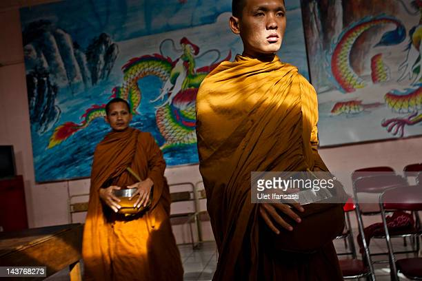 Buddhist monks prepare to receive alms from Buddhist religious members of the public ahead of Vesak Day on May 3 2012 in Magelang Indonesia Buddhists...