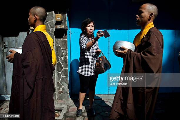 Buddhist monks prepare to receive religious alms from Buddhist members of the public as they walk around the streets ahead of Vesak Day commonly...