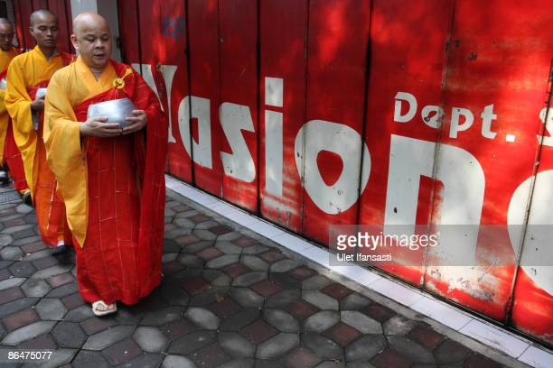 Buddhist monks prepare to receive religious meals from Buddhist members of the public as they walk around the streets on Vesak Day commonly known as...