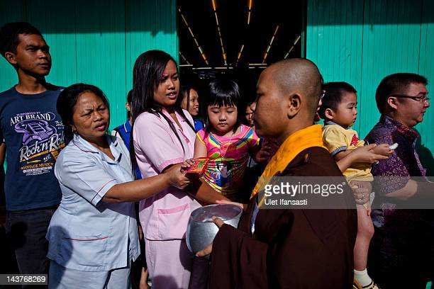 Buddhist monks receive alms from Buddhist religious members of the public ahead of Vesak Day on May 3 2012 in Magelang Indonesia Buddhists in...