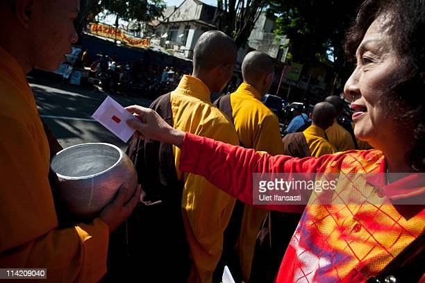 Buddhist monks receive religious alms from Buddhist members of the public as they walk around the streets ahead of Vesak Day commonly known as...