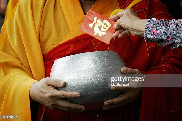 Buddhist monks receive religious meals from Buddhist members of the public as they walk around the streets on Vesak Day commonly known as 'Buddha's...