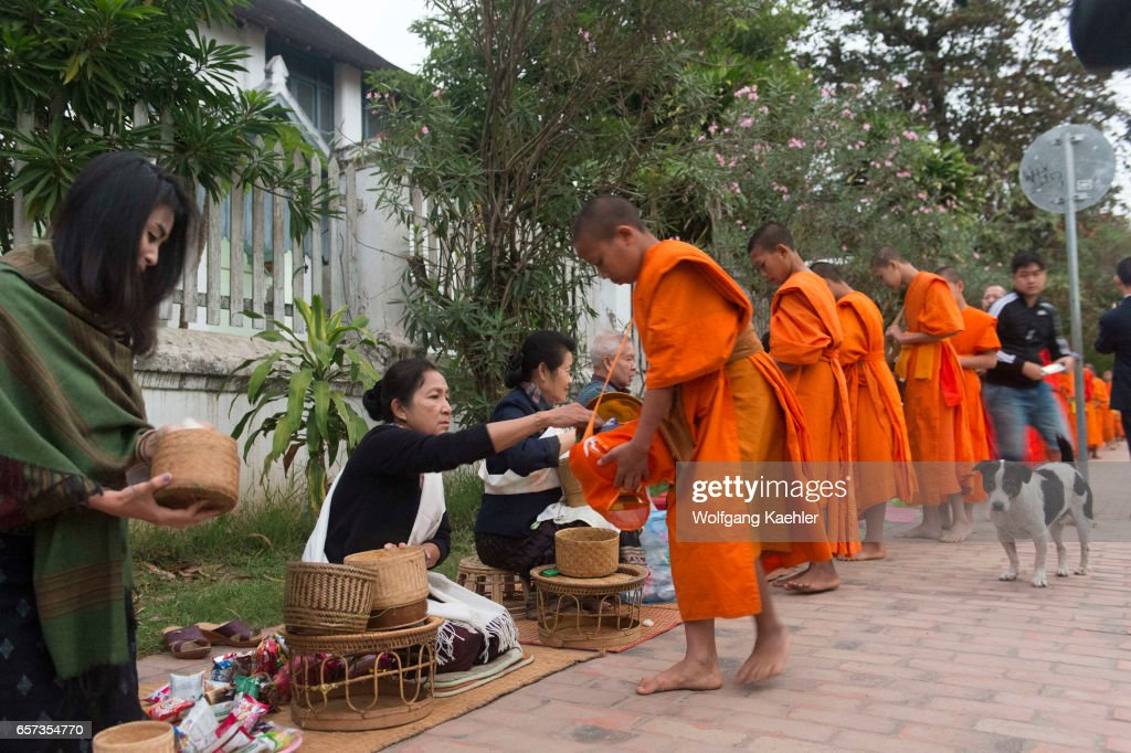 Buddhist monks receiving alms from the people early morning... : Nachrichtenfoto