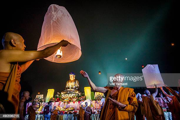 Buddhist monks release a lantern into the air at Borobudur temple during celebrations for Vesak Day on May 15 2014 in Magelang Central Java Indonesia...