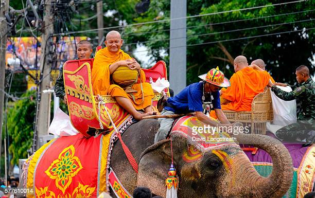Buddhist monks ride atop elephants during a merit making ceremony The annual religious celebration is held to pay homage to King Bhumibol Adulyadej...