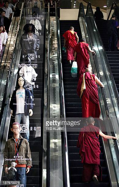 Buddhist monks ride on a escalator where mannequins are displayed to promote designer clothes at a shopping mall in Hong Kong 31 October 2005 Hong...