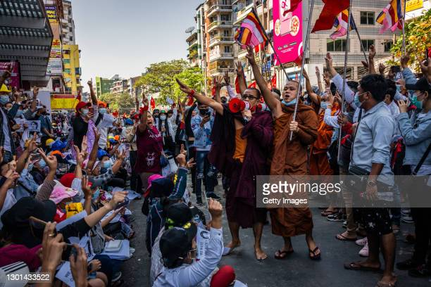 Buddhist monks shout slogans and make three-finger salutes during a protest on February 10, 2021 in Yangon, Myanmar. Myanmar declared martial law in...