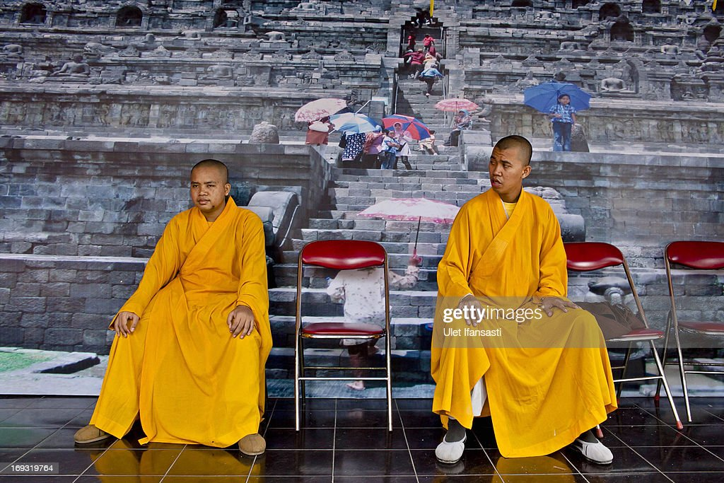 Buddhist monks sits in front of borobudur wallpaper at the temple during Pindapata procession on May 23, 2013 in Magelang, Central Java, Indonesia. As many as 100 monks took to the streets of Magelang city in a procession known as Pindapata, ahead of Vesak day which celebrates the birth of the Lord Buddha.