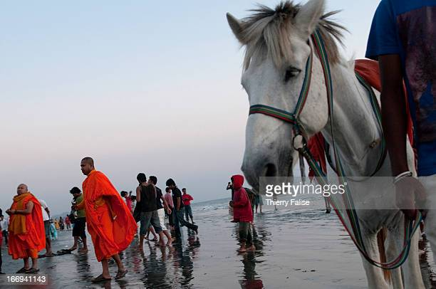 COX'S BAZAR BANGLADESH Buddhist monks stand behind a horse that can be rented for a ride on the Cox's Bazar beach
