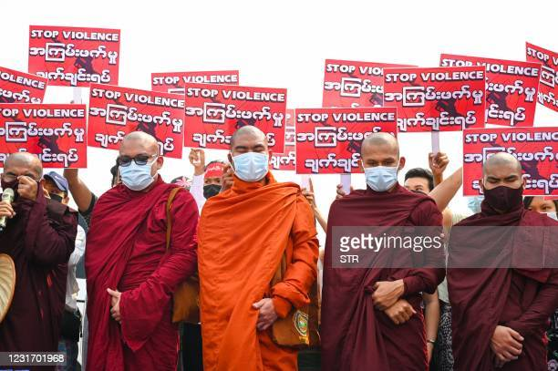Buddhist monks stand in front of protesters holding signs during a demonstration against the military coup in Yangon's Hlaing Tharyar township on...