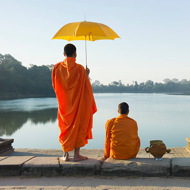 Buddhist Monks standing in front of water