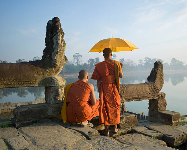 Buddhist monks standing next to stone carvings