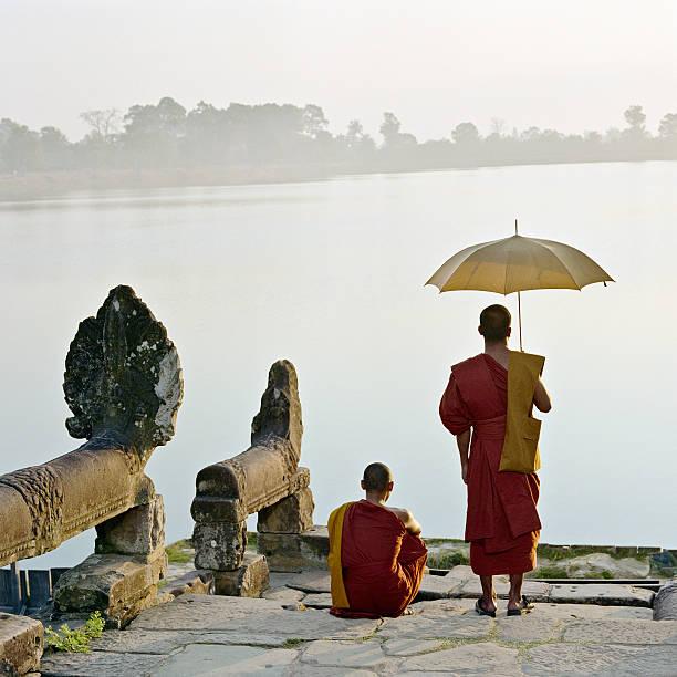 Buddhist monks standing on water's edge