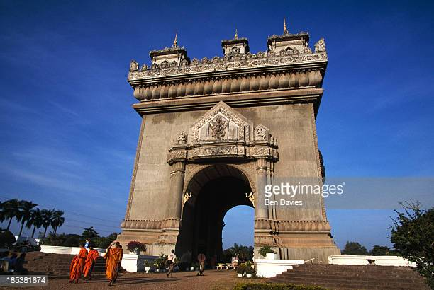 Buddhist monks stroll in front of the Patuxai, a gigantic concrete monument in the centre of Vientiane reminiscent of the Arc de Triomphe in Paris....