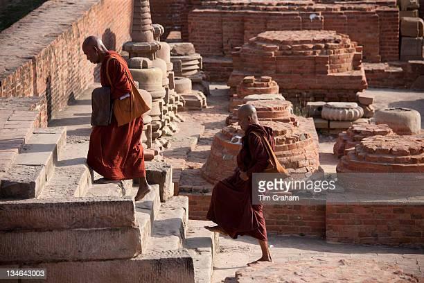 Buddhist monks visiting Dharmarajika Stupa at Sarnath ruins near Varanasi Benares Northern India