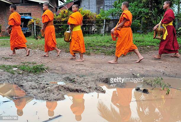 Buddhist monks walk down an alley as they collect alms and bless the local residents in Luang Namtha northern Laos on October 14 2009 About 60% of...