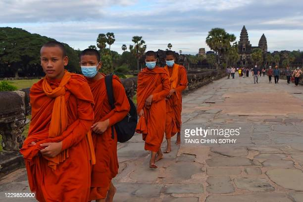 Buddhist monks walk in the compound of the Angkor Wat temple in Siem Reap province on November 29, 2020.