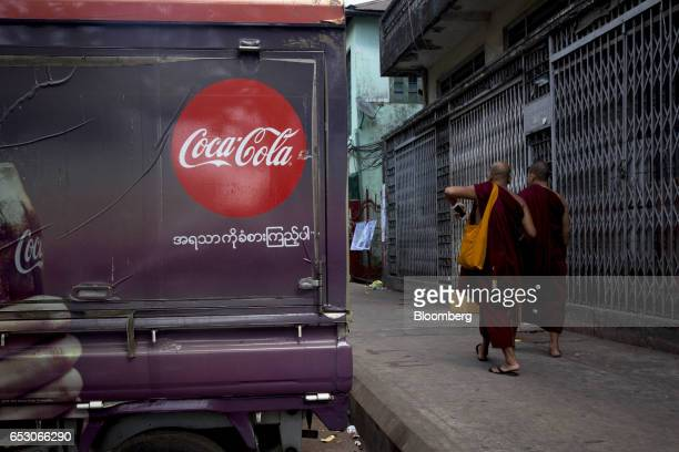 Buddhist monks walk past a truck featuring a Coca Cola advertisement in Yangon Myanmar on Friday March 10 2017 Myanmar is considering changes to the...