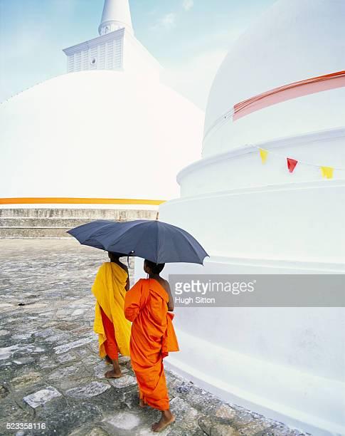 buddhist monks walking amongst the dagobas of anuradhapura - hugh sitton stock-fotos und bilder