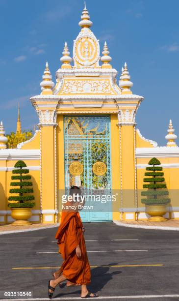 Buddhist Monks walking by a gate in The Royal Palace in Phnom Penh Cambodia.