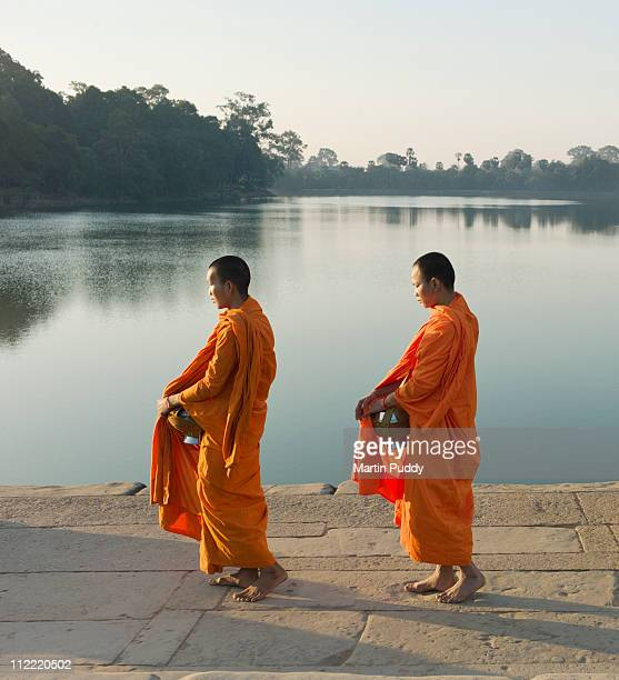 Buddhist Monks walking in front of water edge