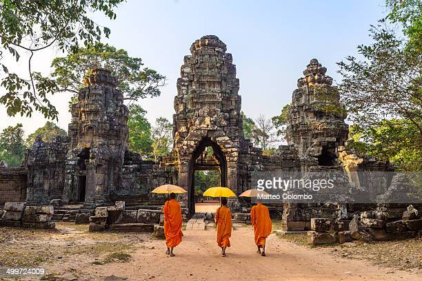 buddhist monks walking inside angkor wat temple - angkor stock photos and pictures