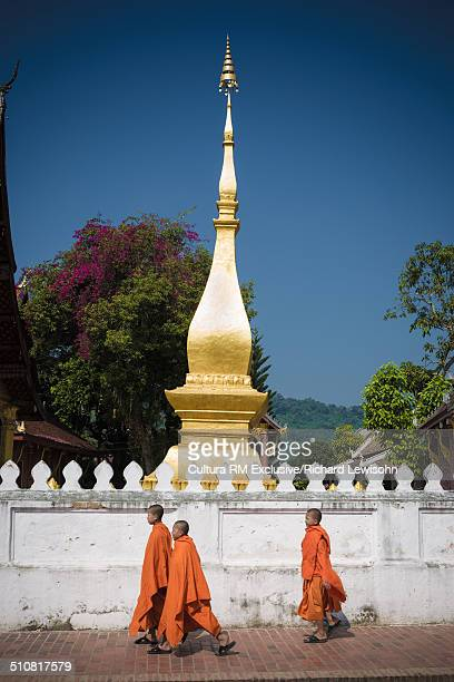 buddhist monks walking next to wat sop temple, sisavangvong road, luang prabang, laos, southeast asia - laotian culture stock pictures, royalty-free photos & images