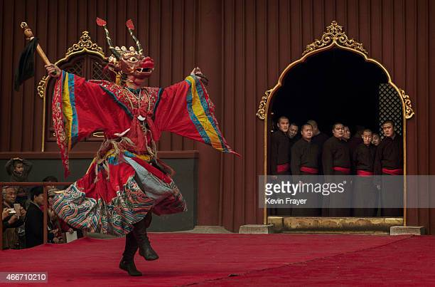 Buddhist Monks watch a dancer perform a Tibetan Buddhist mask dance during a practice for an upcoming ceremony at the Lama Temple or Yonghegong on...