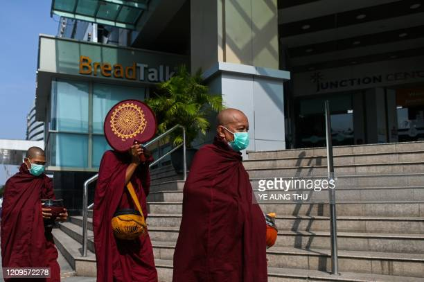 Buddhist monks wearing face masks amid concerns over the spread of the COVID-19 coronavirus walk to collect alms in front of a closed shopping mall...