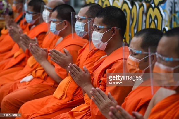 Buddhist monks wearing protective face shields statue as they celebrate Songkran, also known as the Thai New Year, at Wat Pho temple in Bangkok,...