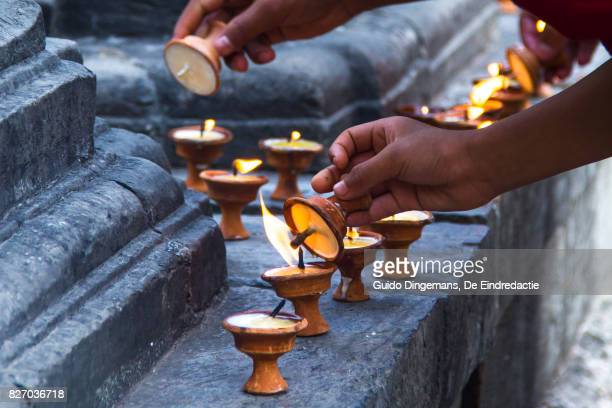 Buddhist novice lights butter lamps at the Monkey Temple in Kathmandu, Nepal