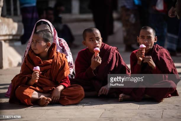 Buddhist novice monks eating ice-cream during Ananda pagoda festival in Bagan, Myanmar on January 9, 2020. Ananda pagoda festival is an annual...