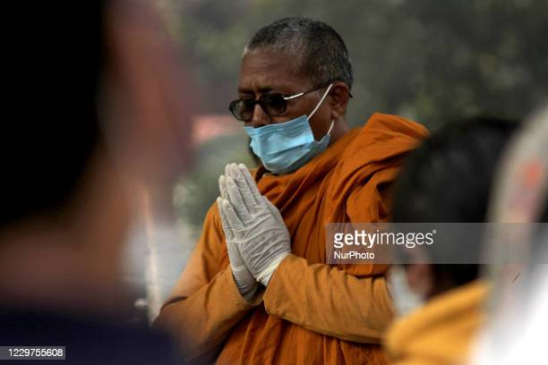 Buddhist nun along with relatives offer prayers before the cremation of a Covid-19 victim, at Nigambodh Ghat crematorium, on November 23, 2020 in New...